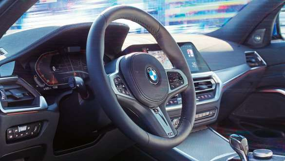 Detailed side view of the cockpit of the BMW 3 Series Sedan with focus on the steering wheel with variable sport steering.