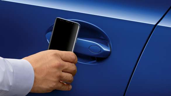 Close-up of the driver's door of the BMW 3 Series Sedan with a Samsung mobile phone held in front of the door handle.
