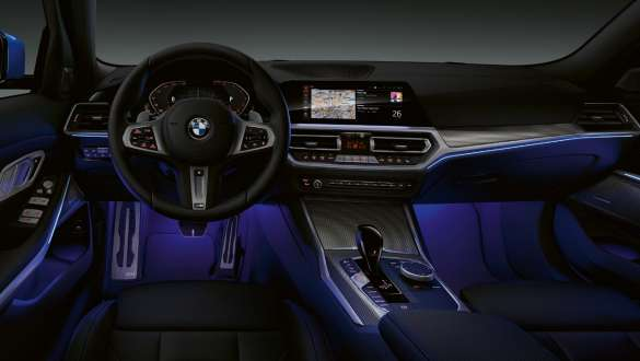 Front view of the driver's cockpit of the BMW 3 Series Sedan with by Ambient light blue illuminated legroom.