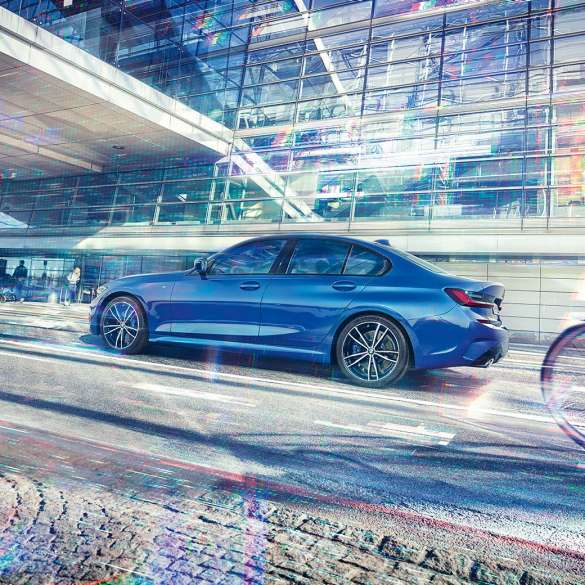 Still shot of the BMW 3 Series Sedan from the side on the day in front of a glass building.