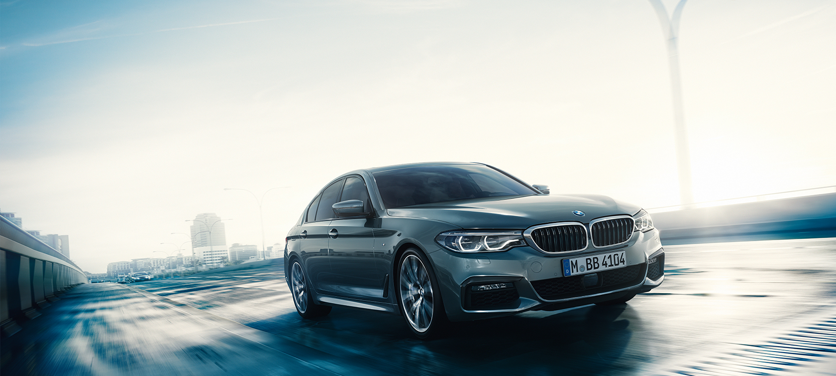 Front view of driving BMW 5 Series Sedan by day under glass building.