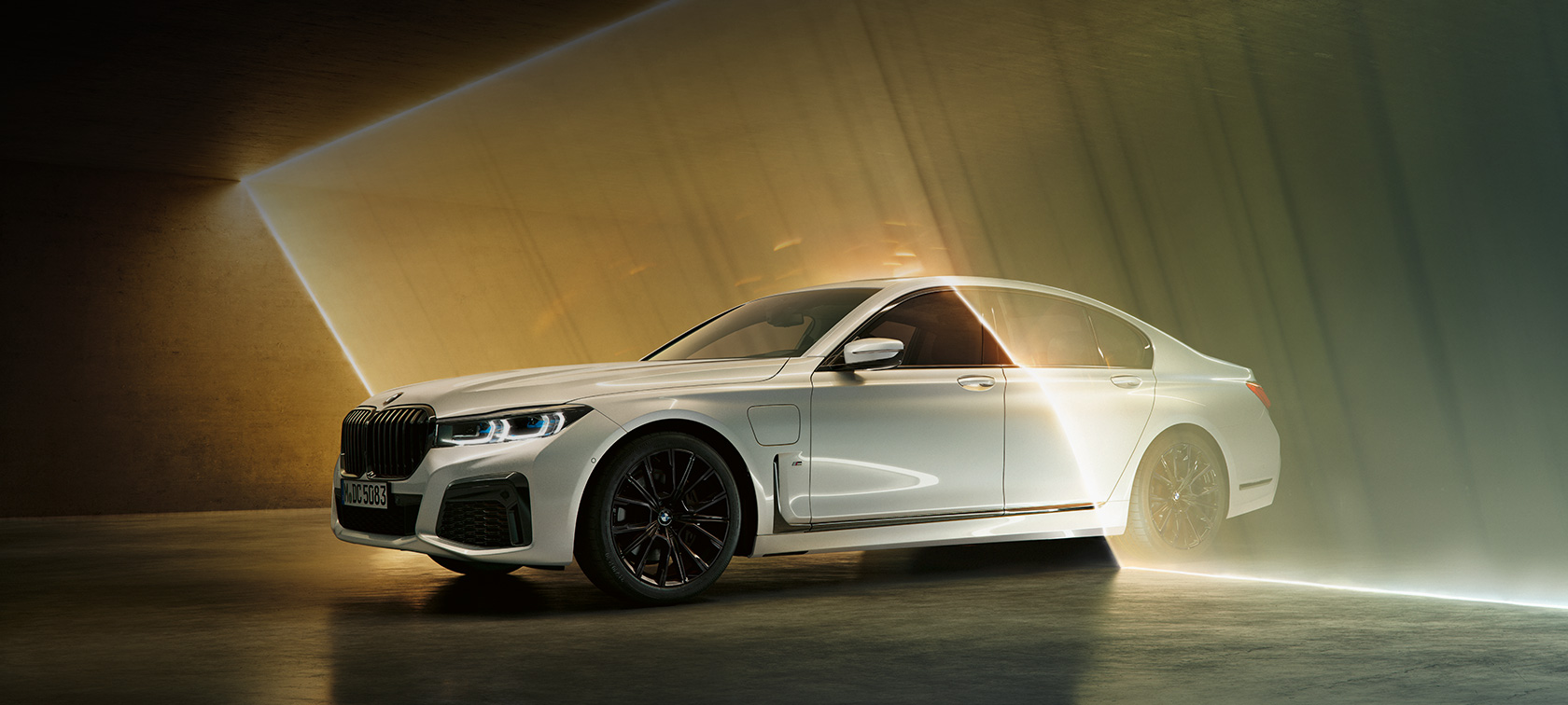 BMW 7 Series Sedan: white BMW in three-quarter front view surrounded by beam of light