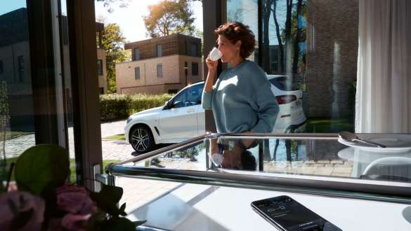 Woman drinking a cup of coffee while she updates the software of her BMW X5 via Remote Software Upgrade G05 2018