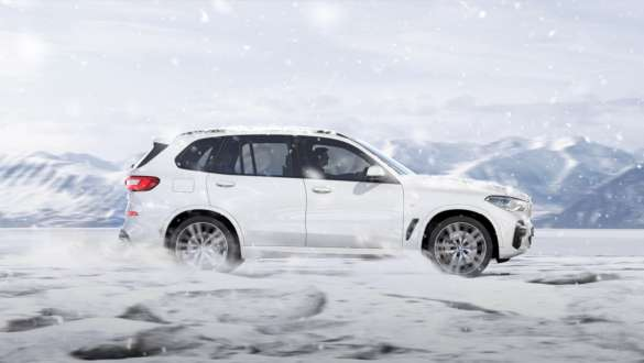 Driving mode xSnow BMW X5 G05 2018 Mineral White metallic side view driving on snow