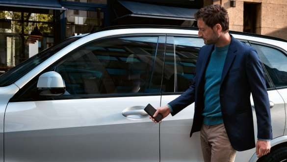 Man opens BMW X5 with smartphone and Digital Key G05 2018
